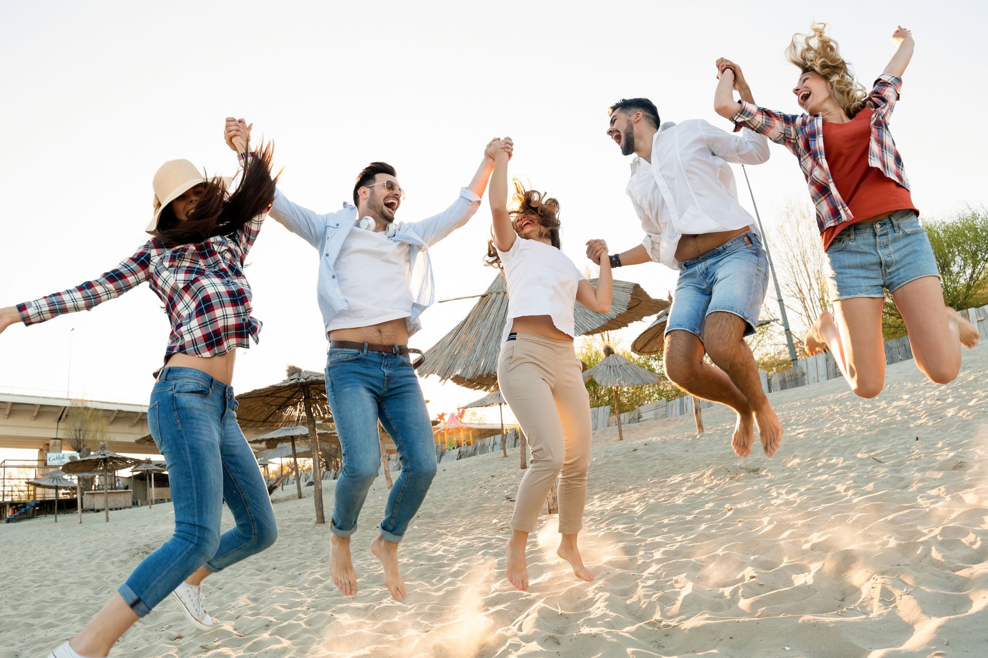 group-of-happy-friends-partying-on-beach-PZDBSTH